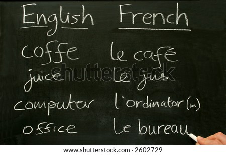 A teacher writing French lesson words on a blackboard. - stock photo