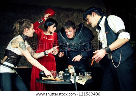 a team of adventurers is making plans at the taverns table - stock photo