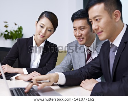a team of asian business people working together in office.