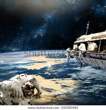 A team of astronauts perform work on a space station while orbiting a large, Earth-like planet. The nearby star shines down on the world below. Elements of this Image Furnished by NASA. - stock photo