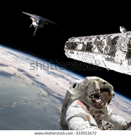 A team of astronauts performing work on a space station while the space shuttle slowly approaches to dock. - Elements of this image furnished by NASA. - stock photo