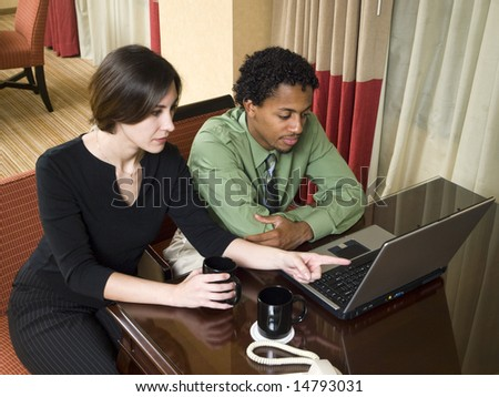 A team of businesspeople review results on a laptop while working late in a hotel room on a business trip.