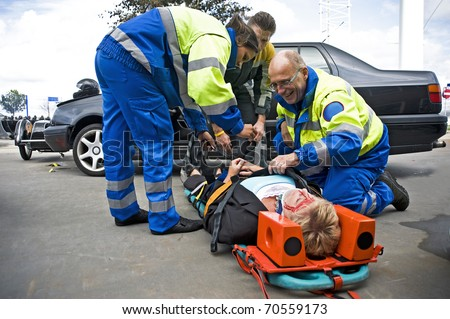 A team of emergency medical services at work, straping an injured driver to a stretcher