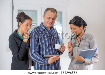 A team of happy businesspeople holding  documents and laptop
