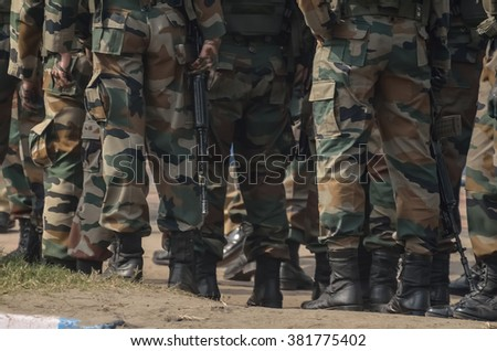 A team of military are walking with assault rifle.