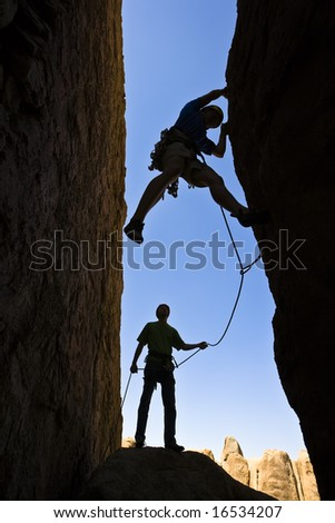 A team of rock climbers are silhouetted as they work their way up a chimney in Joshua Tree National Park. - stock photo