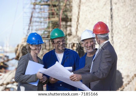 A team of shipping engineers in front of an oil platform in the harbor - stock photo