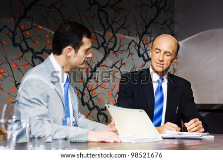 A Team Of Two Executive Business People Plan And Develop Future Business Growth While Looking Through Files And Documents During A Boardroom Meeting - stock photo
