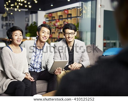 a team of young asian business people talking to boss in office. - stock photo