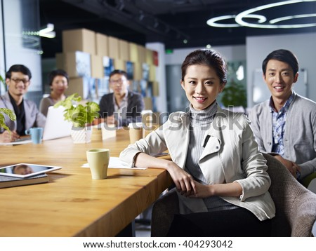 a team of young asian entrepreneurs posing in meeting room. - stock photo