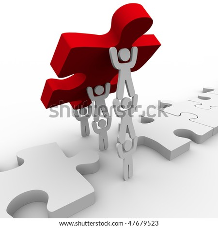 A team works together to lower the final puzzle piece - stock photo