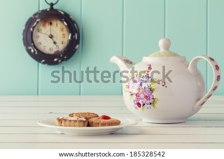 A teapot, a plate with some german cookies and a clock in the background. Five o'clock. Tea time. Robin egg blue background. Vintage look. - stock photo