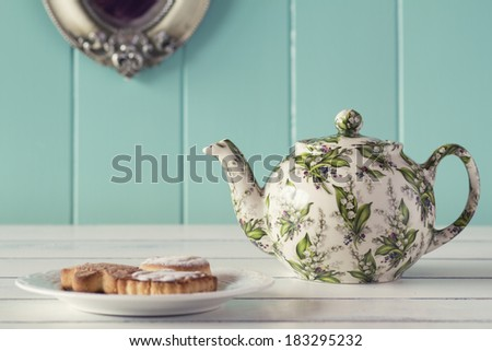 A teapot and a plate with some german cookies.Tea time. Robin egg blue background. Vintage look. - stock photo