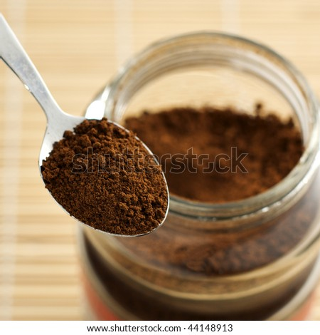 a teaspoon of instant coffee with an open jar in the background - stock photo