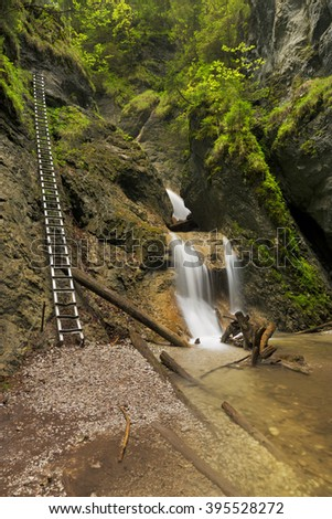 A technically aided trail along a waterfall in the lush Sucha Bela gorge in Slovensky Raj in Slovakia. - stock photo