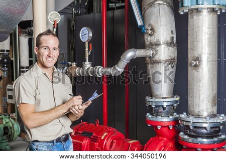 A Technician inspecting heating system in boiler room - stock photo