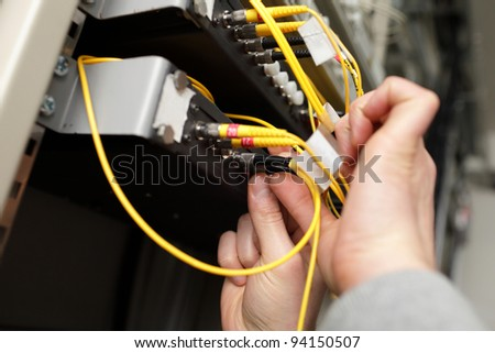 A technician with optical connector at telecom site - stock photo