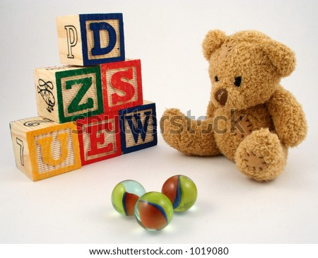 A teddy bear, wooden blocks and marbles - stock photo