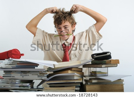 A teen behind of desk tearing his hair - stock photo