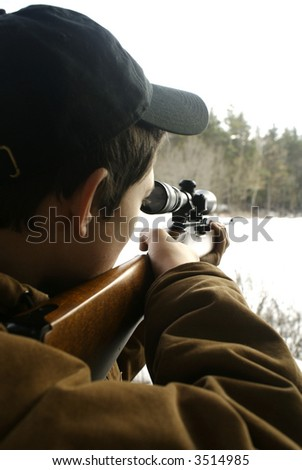 a teen boy hunting in the woods in winter - stock photo