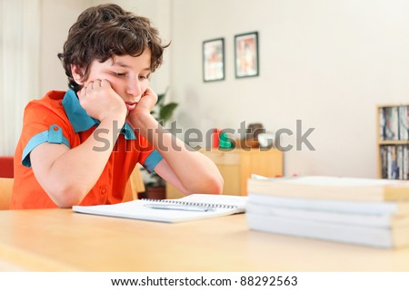 A teen boy learning over his homework reading his workbook. - stock photo