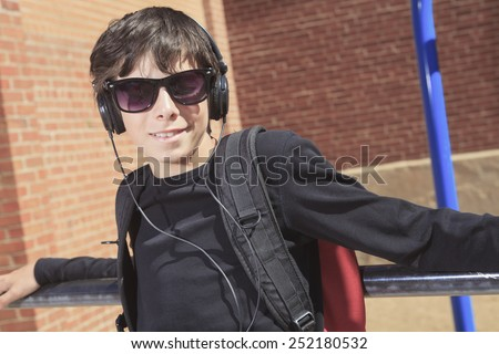 A teen boy listening to music with sun glasses - stock photo
