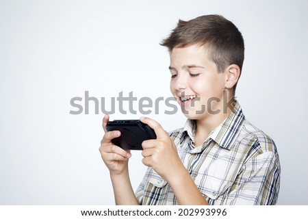 A teen boy playing video games in a portable game console against gray background - stock photo