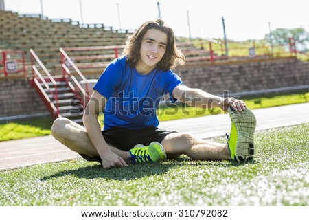 A teen boy ready to run outside on a training field