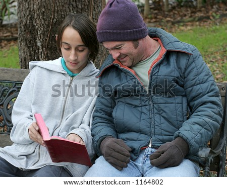 A teen boy sharing the bible with a homeless man. - stock photo