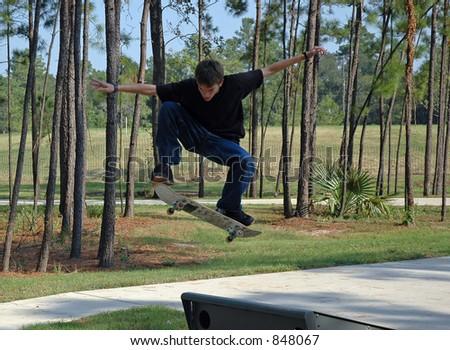 A teen boy soars through the air at a suburban skatepark - stock photo