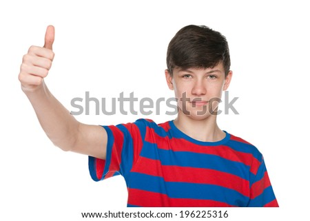 A teen boy with shows thumb up against the white background - stock photo