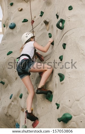 A teen girl climbing on a rock climbing wall with safety harness and helmet on. - stock photo