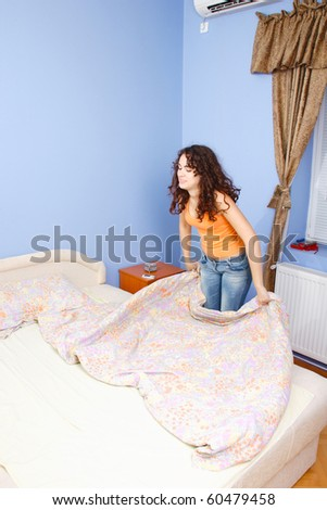 A teen girl happily making her bed in her room. - stock photo