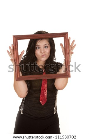A teen girl holding up a picture frame making a silly face while she is wearing a red tie and suspenders. - stock photo