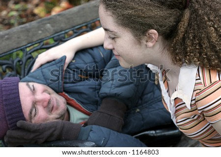 A teen girl volunteering to help the homeless.  Focus on the girl. - stock photo