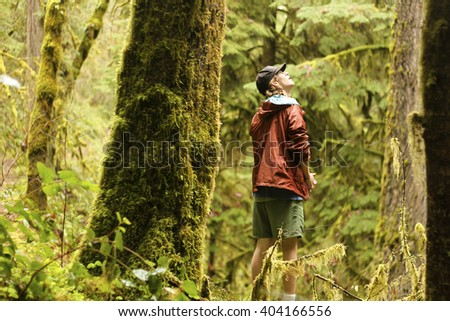 A teen looking up at some trees in the outdoors - stock photo