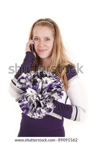 A teen talking on her phone in her cheerleader outfit. - stock photo