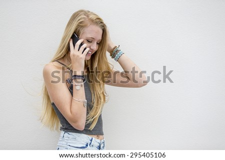 A teenage blonde model posing outdoors on a cellphone - stock photo