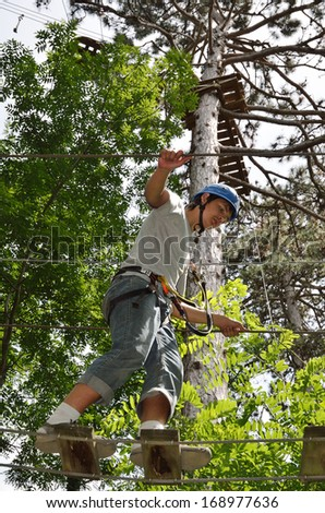 A teenage boy is moving up on the rope ladder. He is photographed from below.