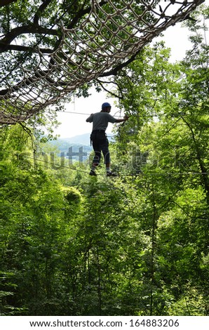 A teenage boy is walking on the tightrope at the rope parkour high up. He is photographed against the forest. - stock photo