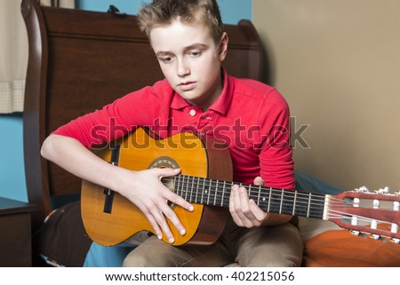 A teenage boy playing guitar in bedroom