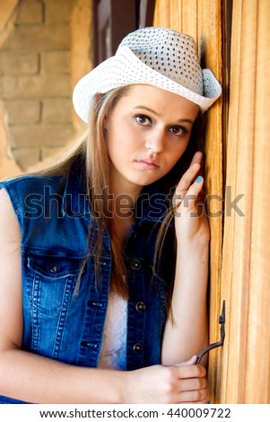 A teenage cowgirl leans against a wood door with a serious look on her face.  Her big, brown eyes are wide and questioning. - stock photo