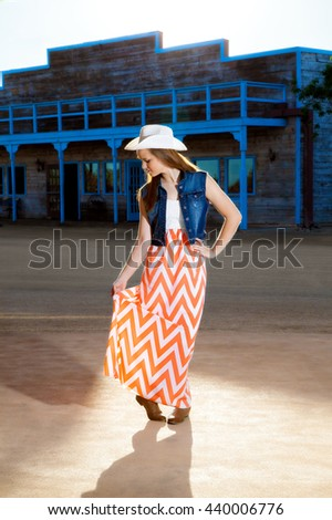 A teenage cowgirl looks down as she gives a little curtsy.  She is wearing a western hat, boots, and a long, modern skirt. - stock photo