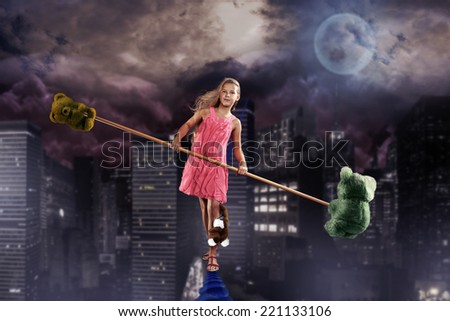 a teenage girl as a tightrope walker over the night town - stock photo