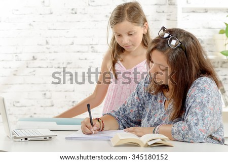 a teenage girl doing her homework with her little sister - stock photo