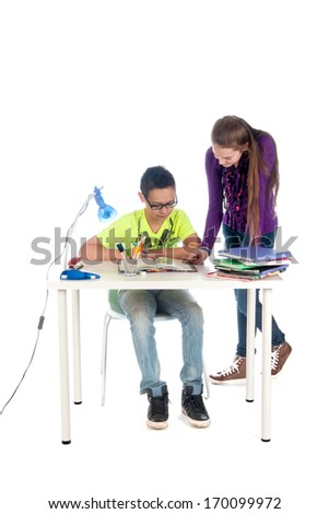 A teenage girl is helping a teenage boy with his homework - stock photo