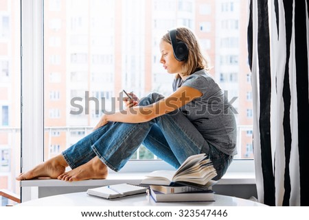 A teenage girl sits on window sill listening to music and looking at her smartphone - stock photo