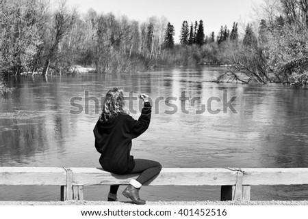 A teenage girl sitting on a wood railing looking out toward a river surrounded by forest of bare trees in black and white spring landscape - stock photo