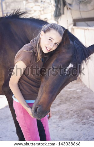 A teenage girl with her horse. Candid photo, happy feeling, best friends - stock photo