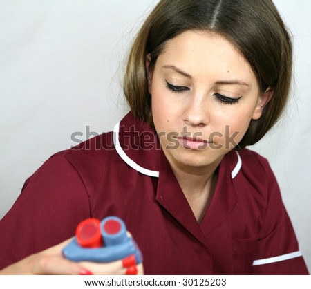 A teenage nursing student looks at a model of a heart - stock photo